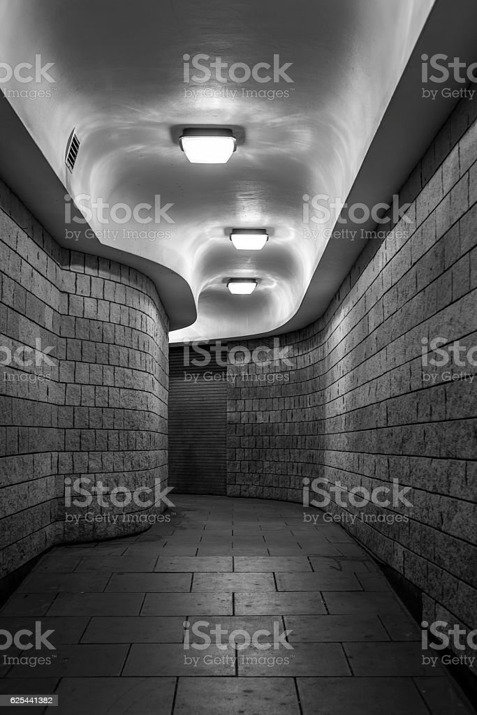Curving pedestrian tunnel (subway), at night - black and white stock photo