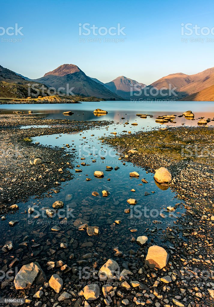 Curving River Leading Out To Lake With Mountain Peaks. stock photo