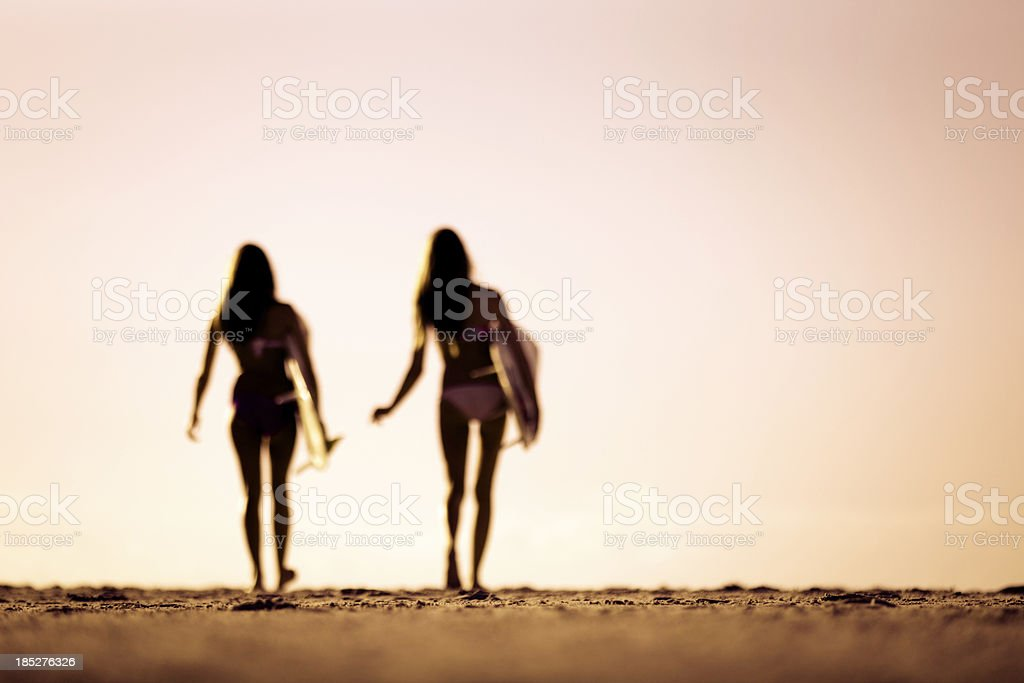 Curvy silhouettes of two women heading out for a surf stock photo