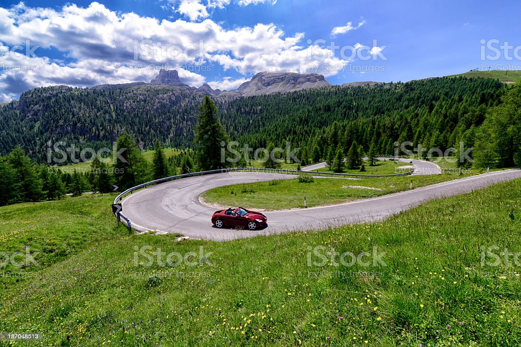 A curvy winding road and a red travelling vehicle stock photo