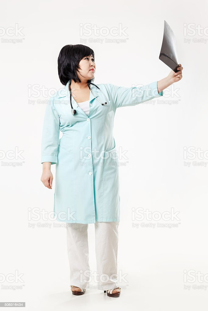 Curvy woman doctor standing considers the results of radiology department stock photo
