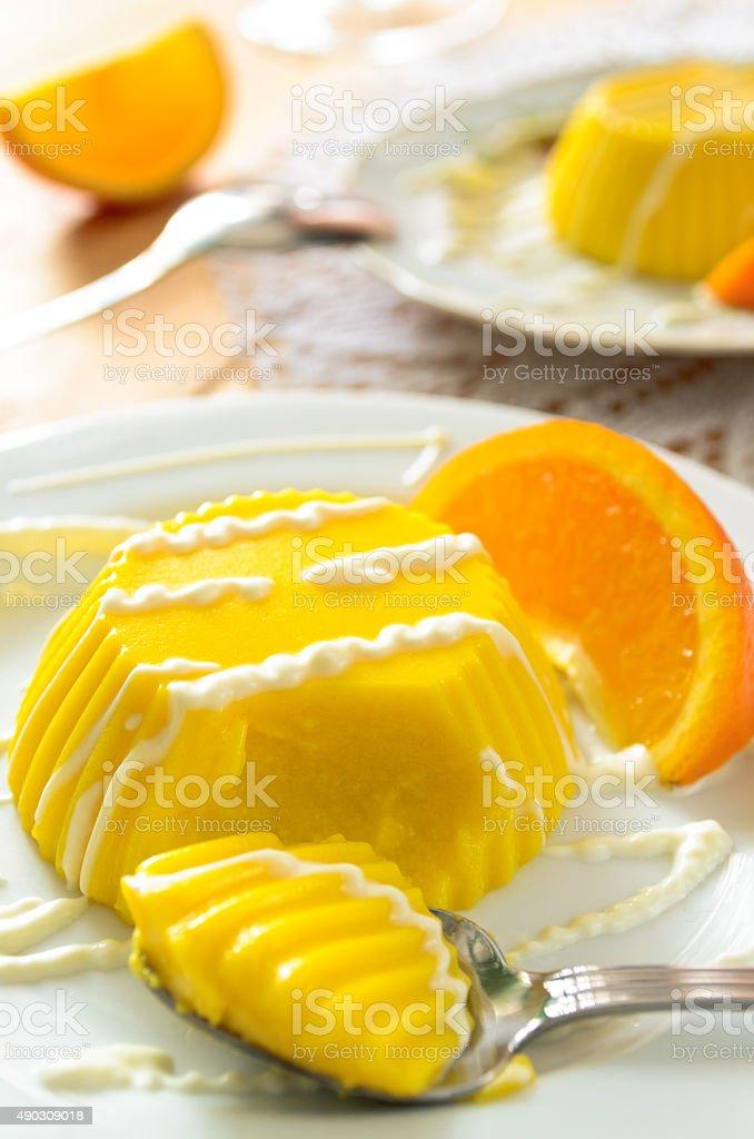 custard pudding with vanilla sauce and orange stock photo