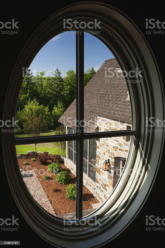 Custom oval window and view to backyard. stock photo