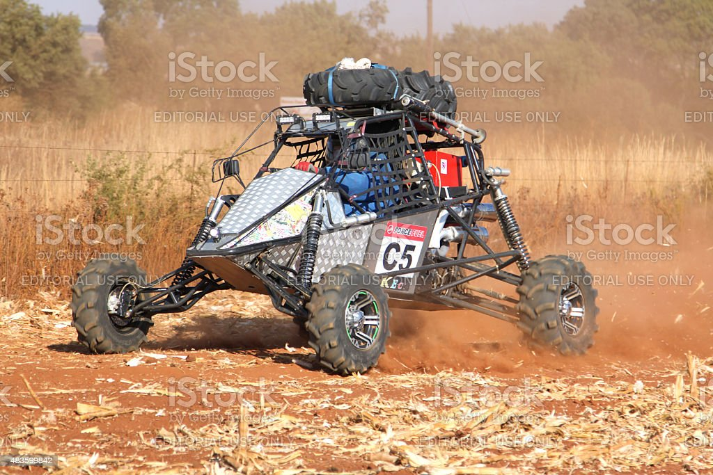 Custom single seater rally buggy kicking up trail of dust stock photo