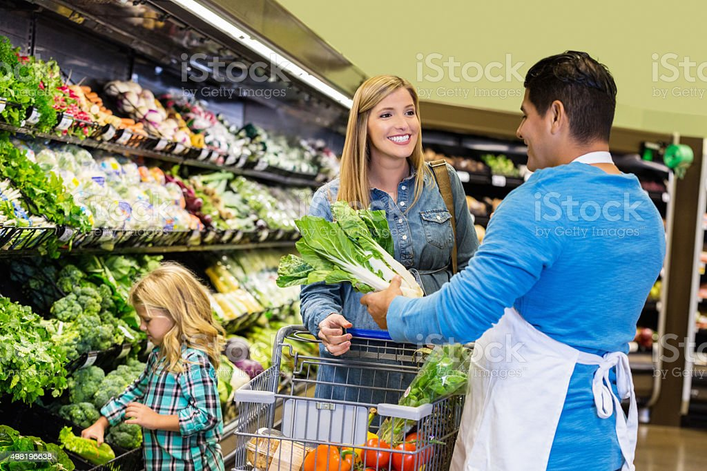 Customer asking produce manager for help in supermarket stock photo