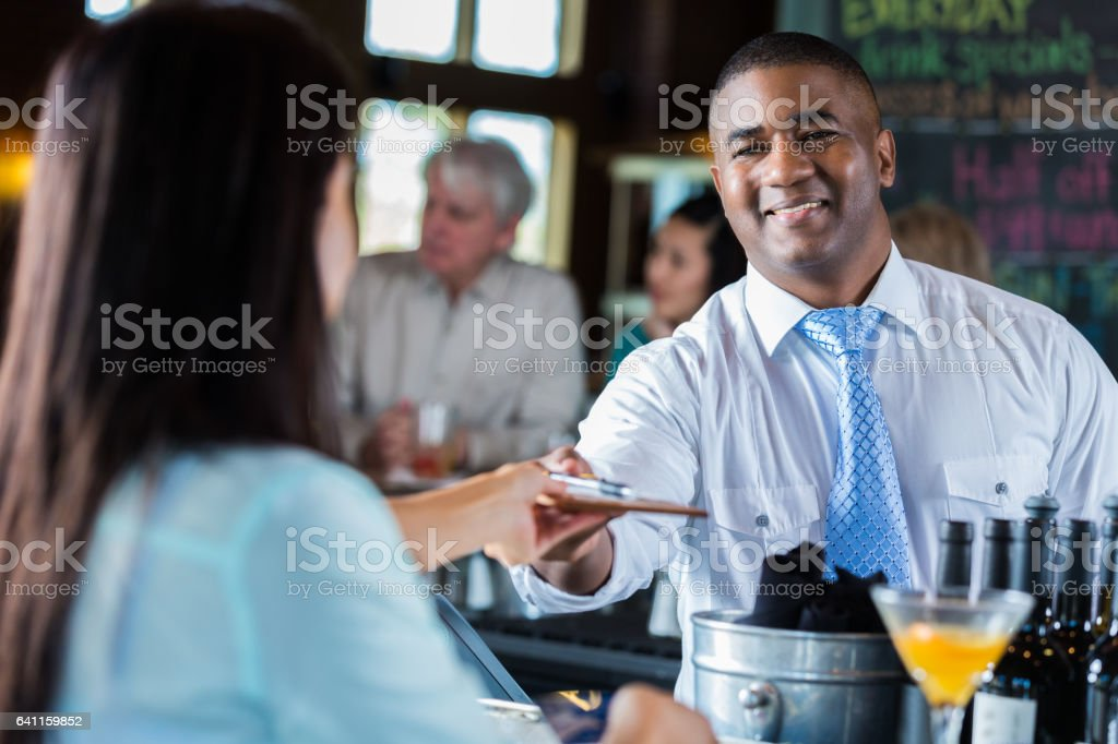 Customer at a bar hands bartender signed credit card receipt stock photo
