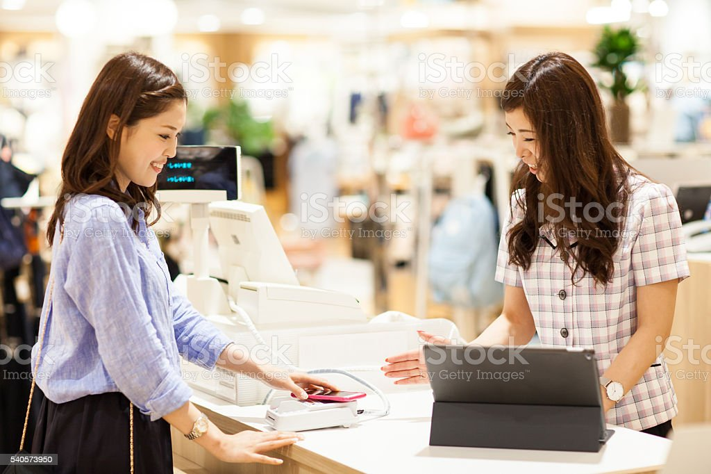 Customer at department store paying by NFC via smart phone stock photo