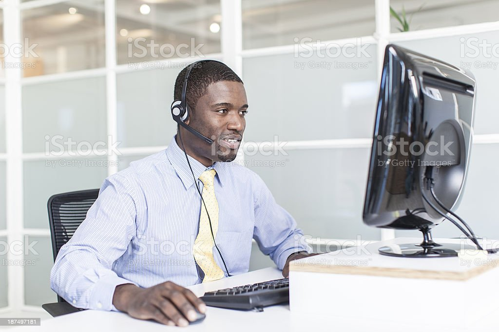 Customer care representative wearing headset and typing royalty-free stock photo