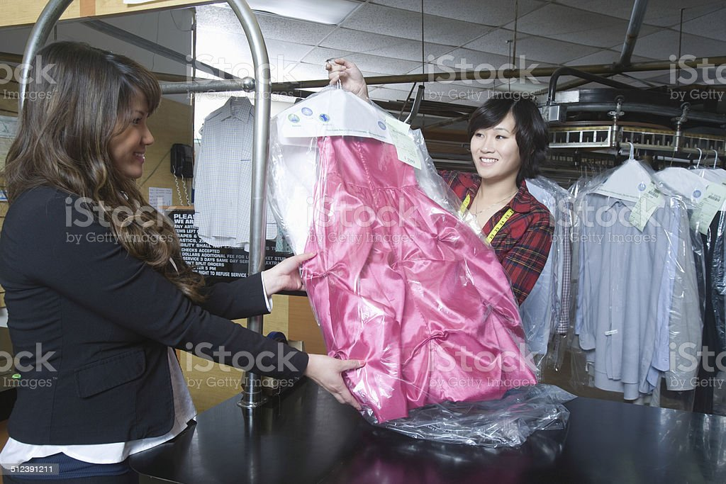 Customer Collecting Clean Dress From Owner In Laundry stock photo