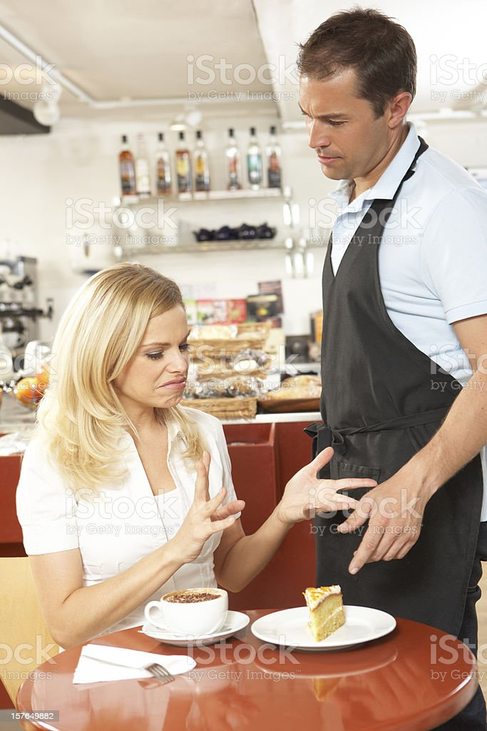 Customer Complaining to Waiter In Coffee Shop stock photo