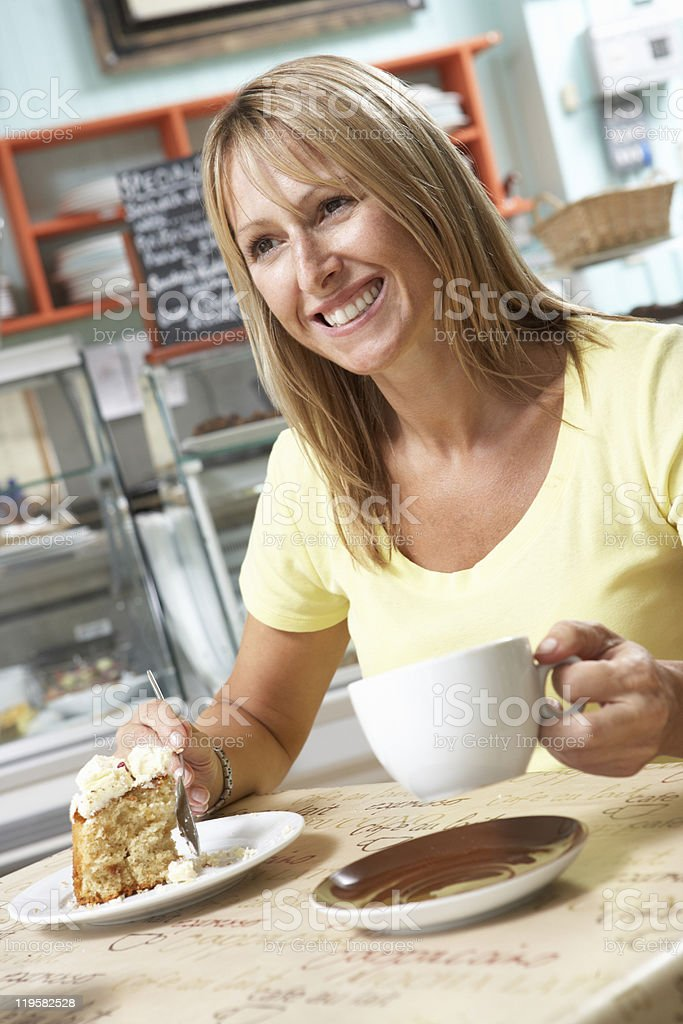 Customer Enjoying Slice Of Cake And Coffee In Caf royalty-free stock photo