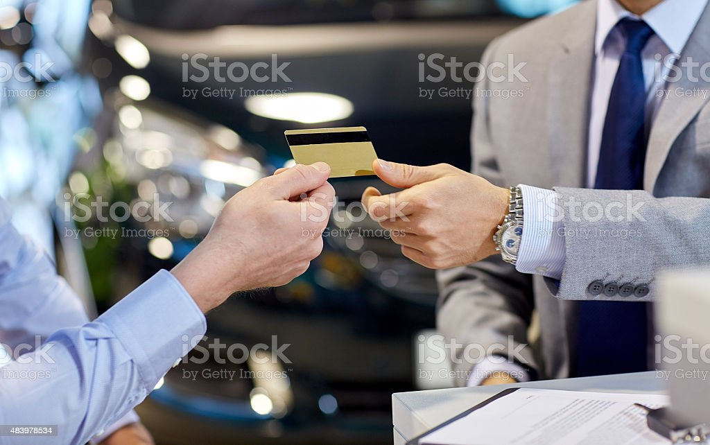 customer giving credit card to car dealer in salon stock photo
