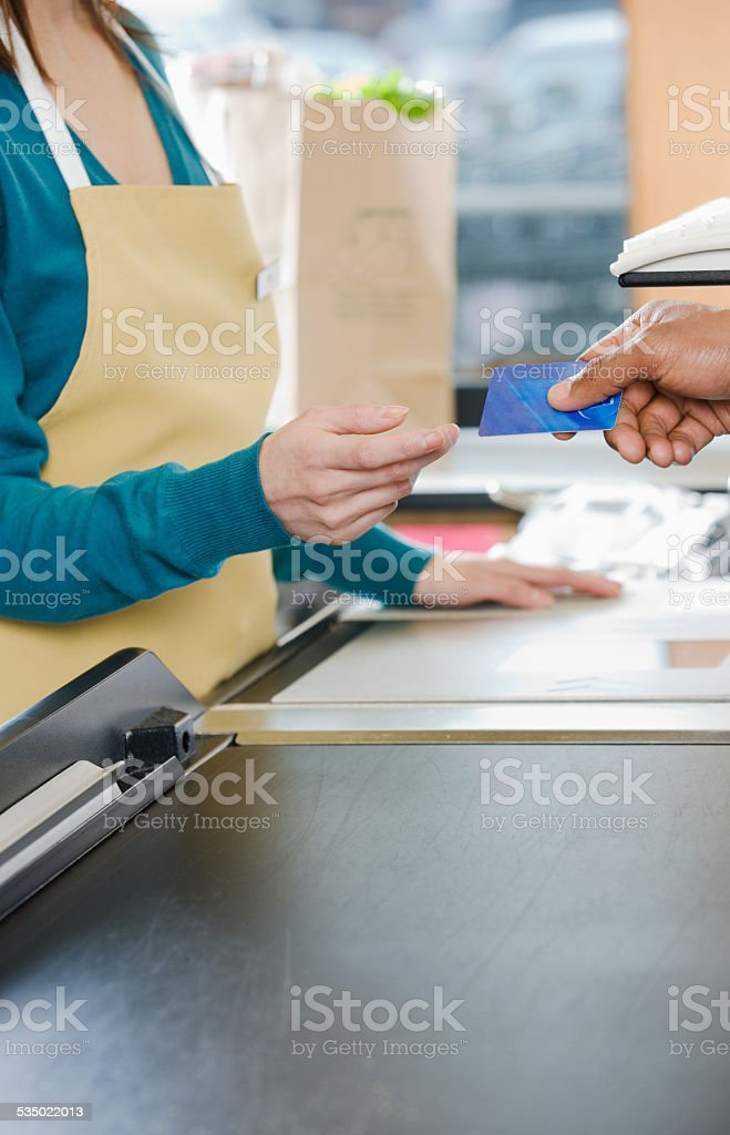 Customer handing a sales assistant a credit card stock photo