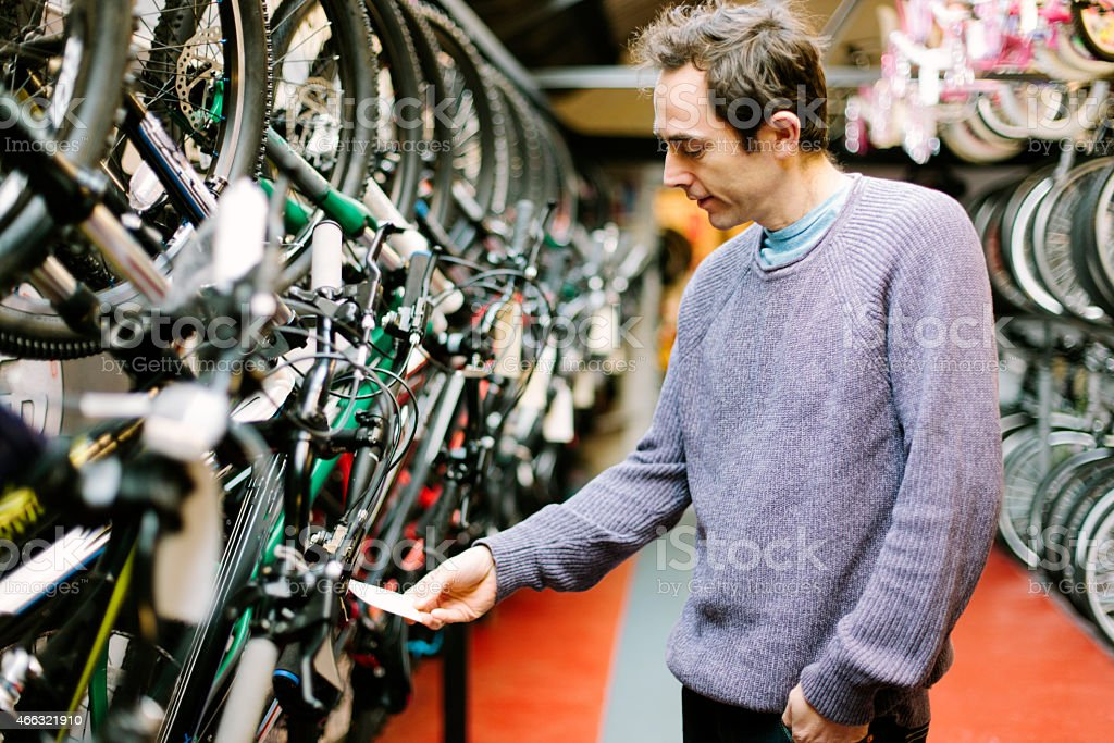 Customer in a bicycle shop, looking at the price tag stock photo