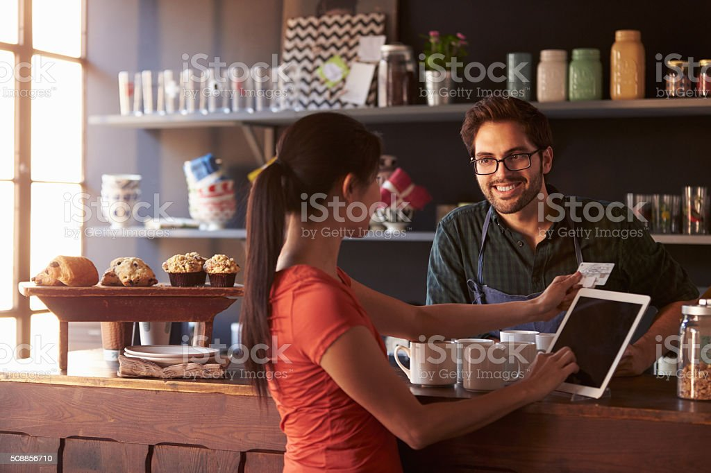 Customer In Coffee Shop Paying Using Digital Tablet Reader stock photo