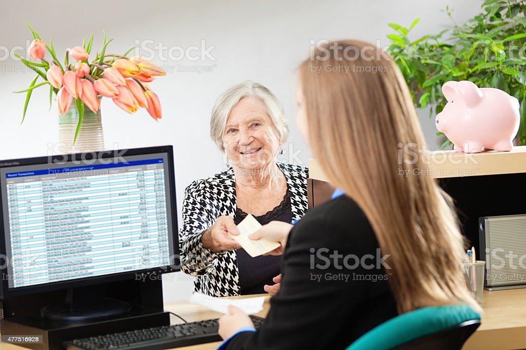 A senior woman bank customer making a financial transaction with a...