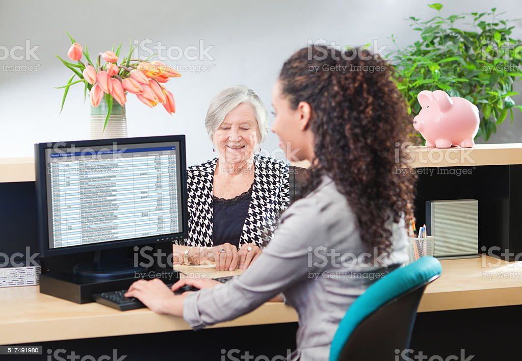 Customer in Retail Banking Counter Window with Bank Teller stock photo