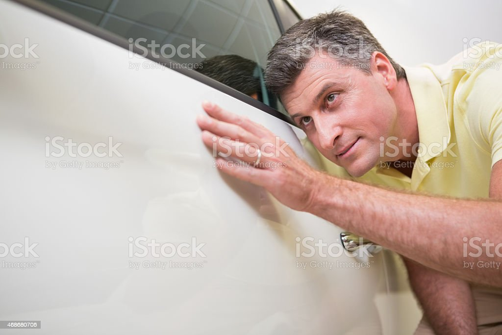 Customer looking at the white cars body stock photo