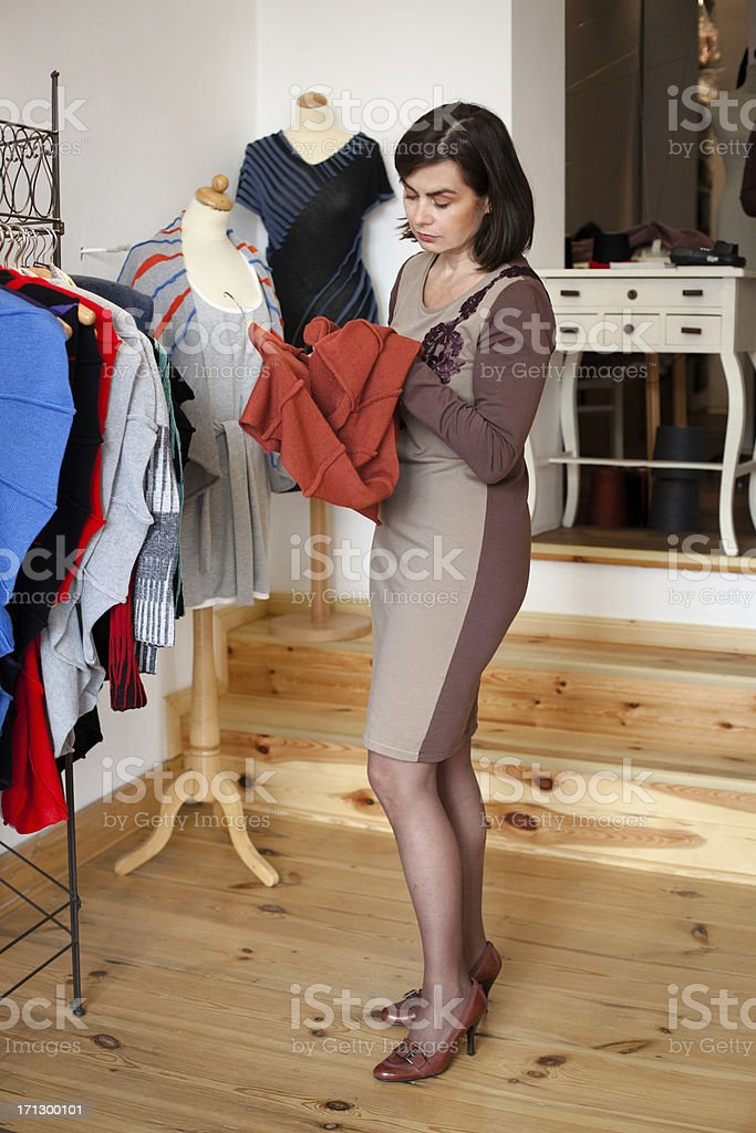 Customer looks at fashion clothing into a small Boutique royalty-free stock photo