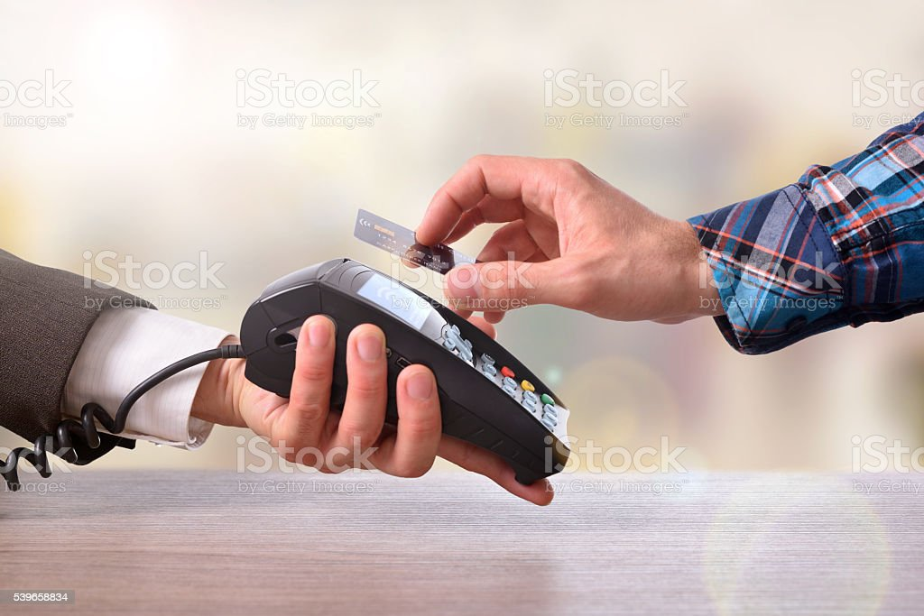 Customer paying a merchant with contactless card front view stock photo