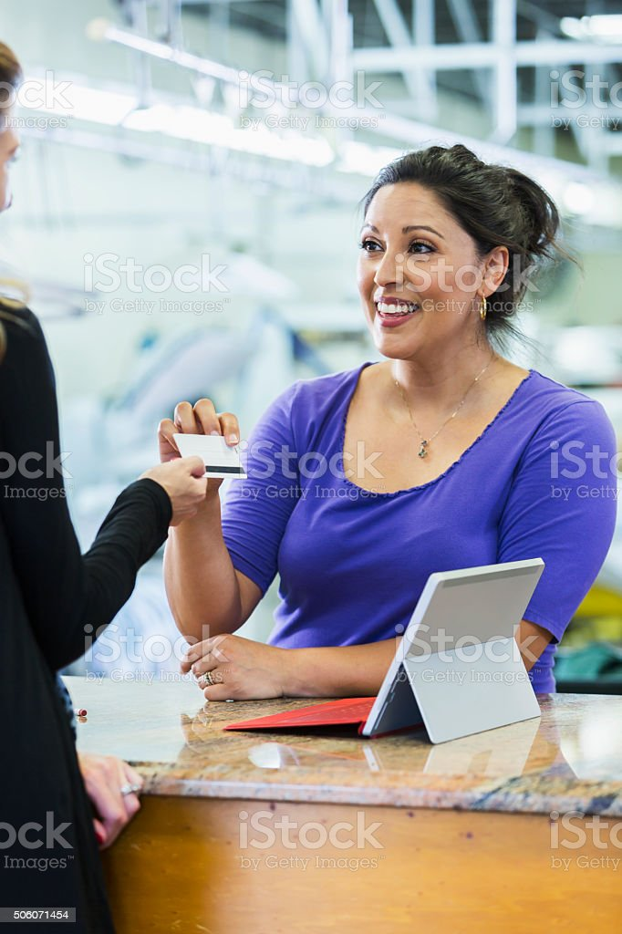 Customer paying for dry cleaning handing card to cashier stock photo