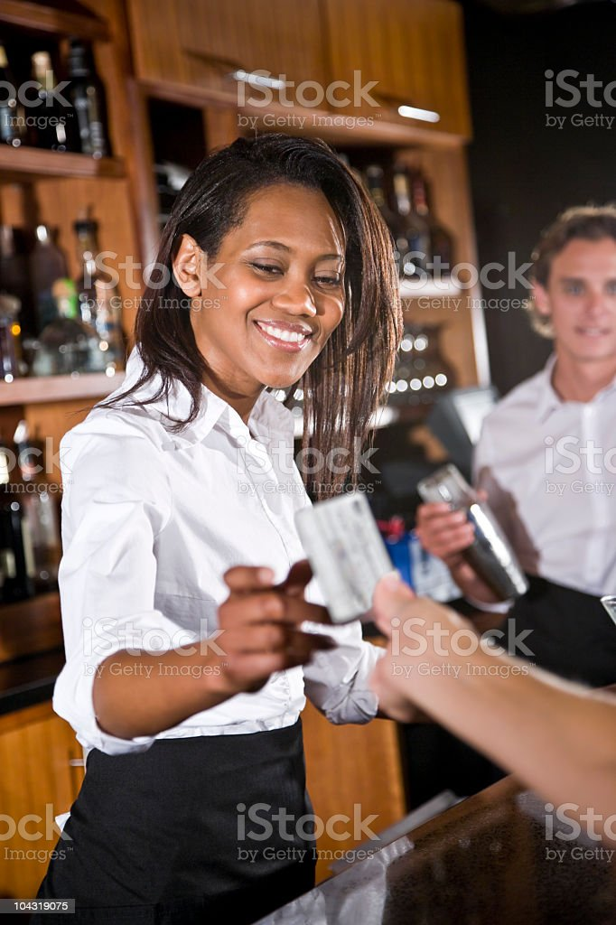 Customer paying, handing credit card to smiling African-American female bartender royalty-free stock photo