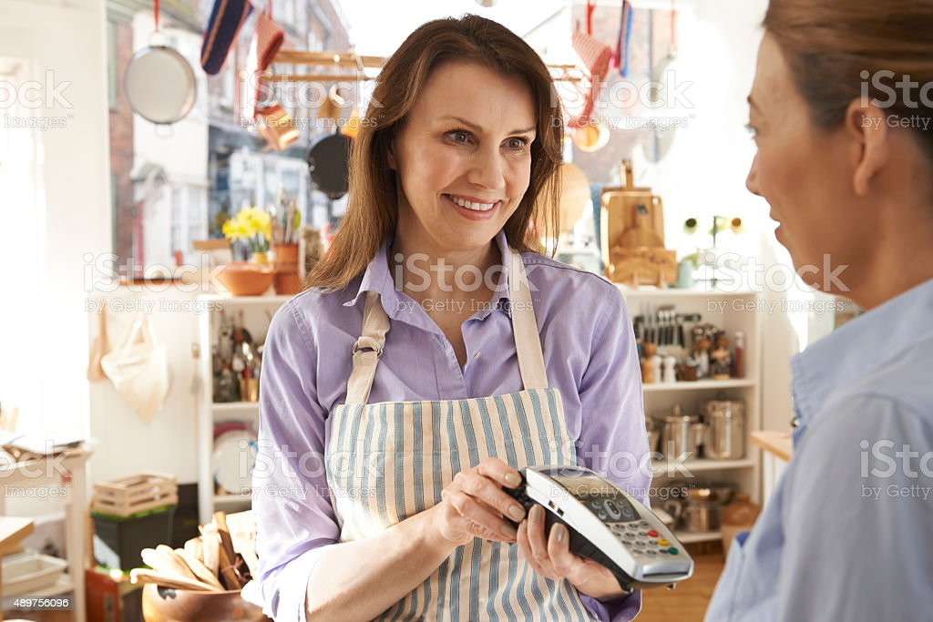 Customer Paying In Kitchen Shop Using Credit Card Terminal stock photo