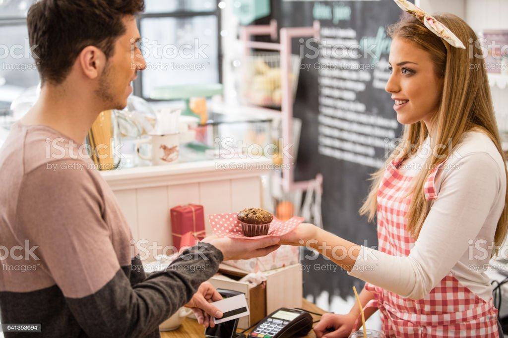 Customer paying muffin with credit card stock photo