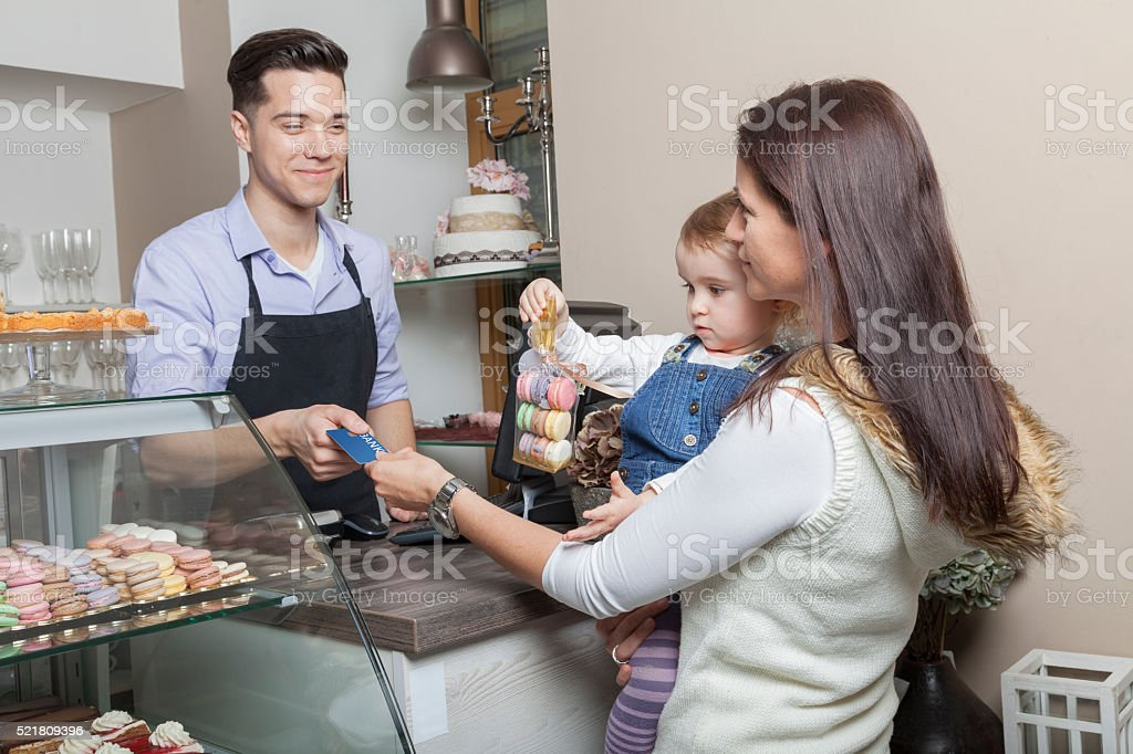 Customer pays with credit card french macaroons cash desk stock photo