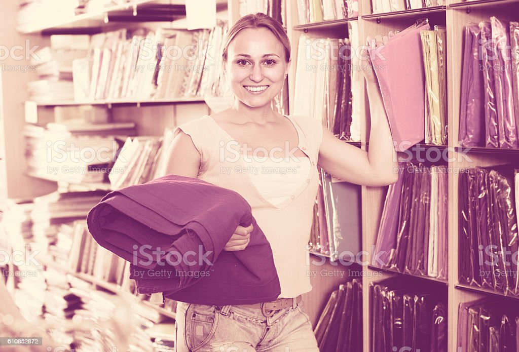 american woman customer picking bedding set in package in textile...