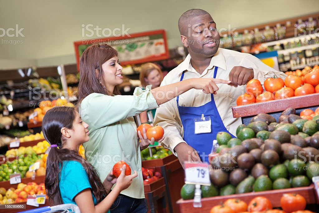 Customer pointing to tomatoes with supermarket produce manager royalty-free stock photo