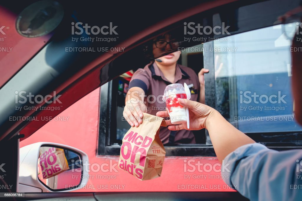 Bangkok, Thailand - Mar 4, 2017: customer receiving hamburger and ice cream after order and buy it from McDonald's drive thru service stock photo