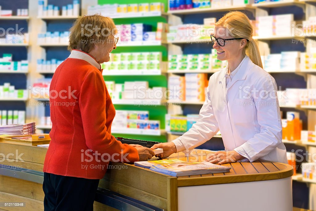 Customer receiving medication from pharmacist. stock photo