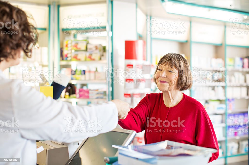Customer receiving medication from pharmacist stock photo