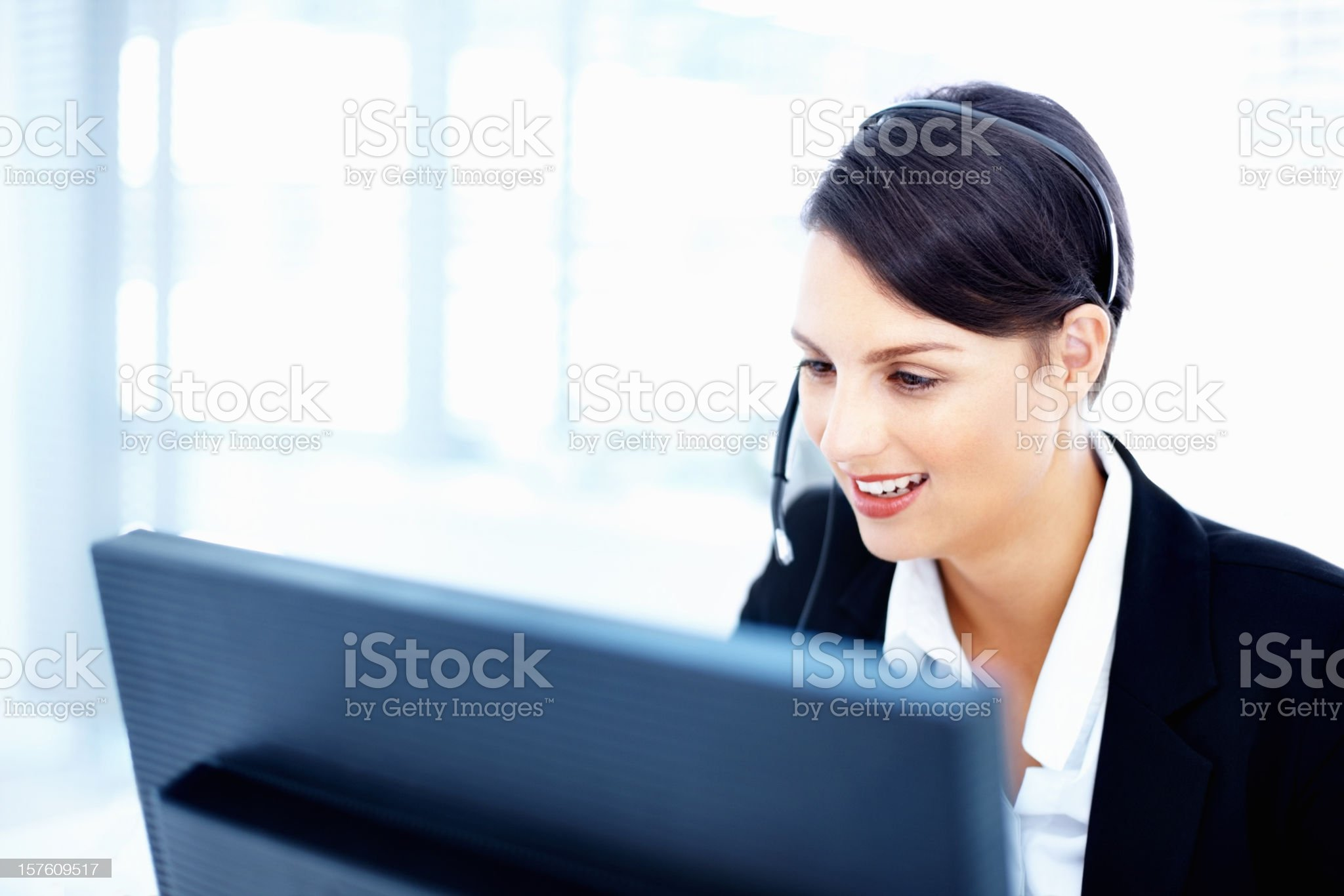 Customer representative wearing headset and working on computer royalty-free stock photo