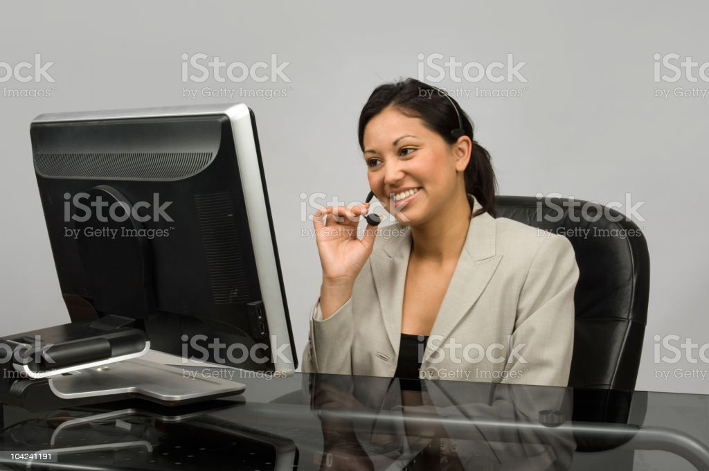Customer service agent smiling while talking on phone stock photo