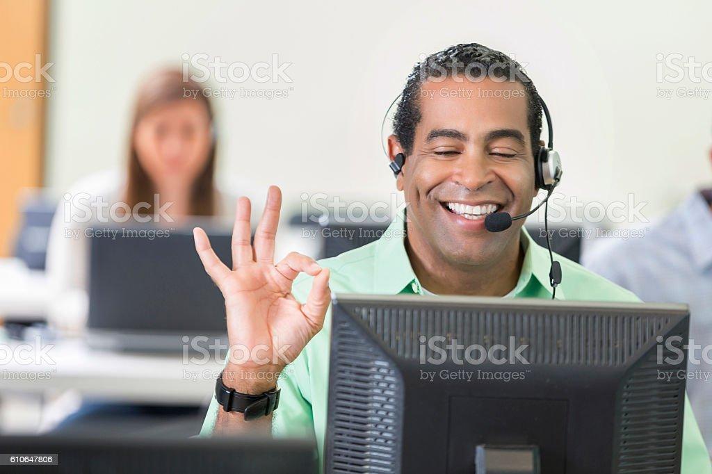 Customer service representative makes 'OK' sign with hand stock photo