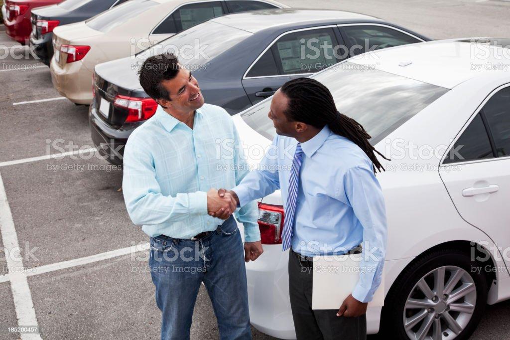 Customer shaking hands with car salesman stock photo