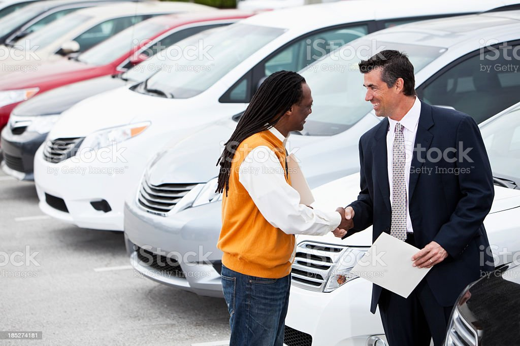 Customer shaking hands with car salesman stock photo
