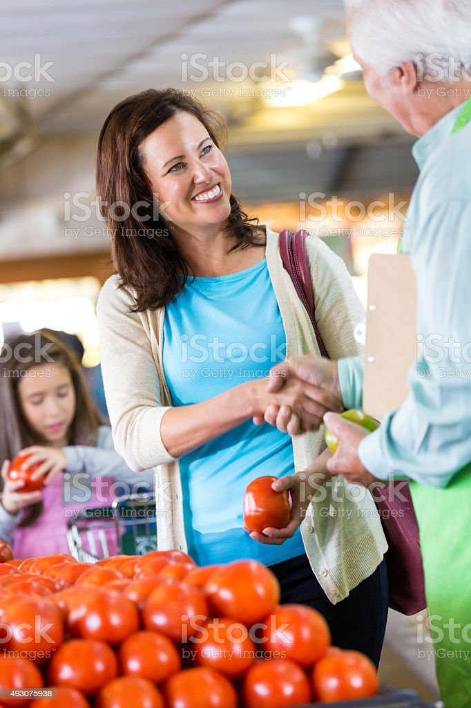 Customer shaking hands with senior grocery store owner stock photo