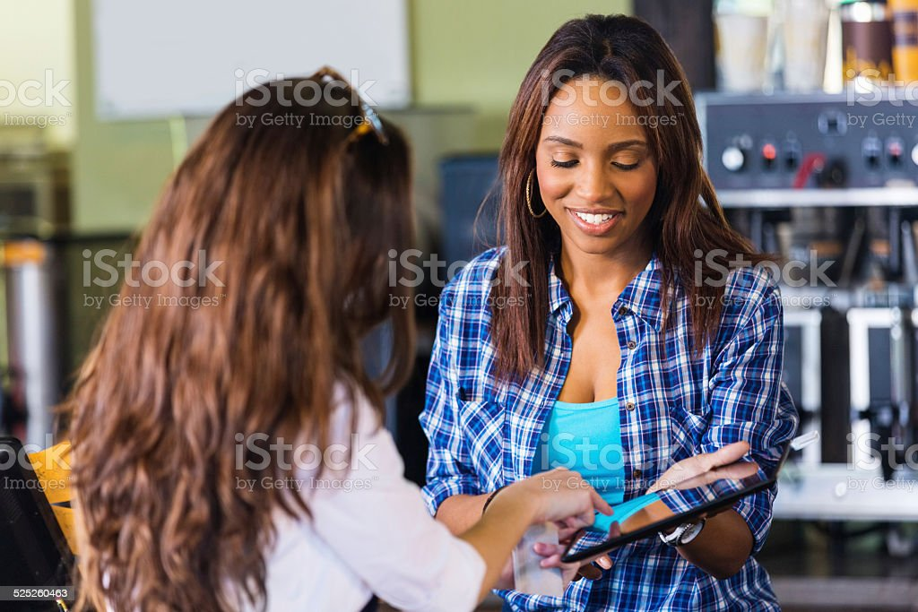 Customer signing digital credit card receipt on tablet