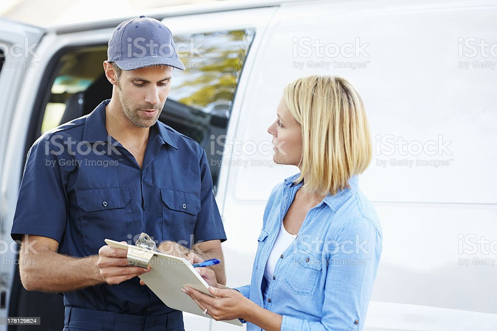 A customer signing for a delivery from a courier stock photo