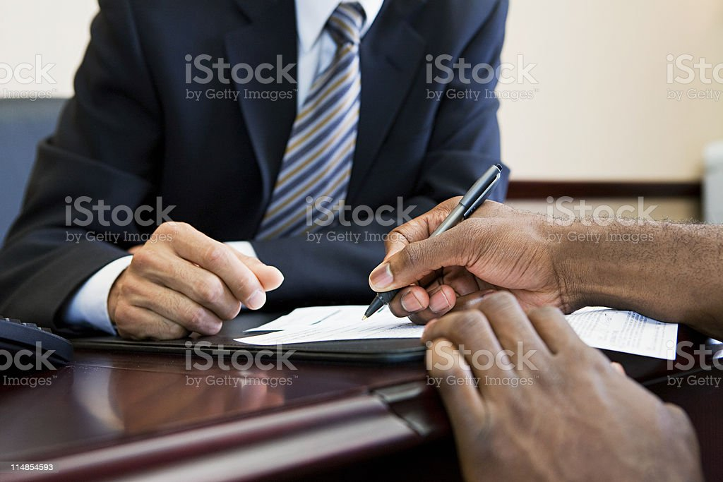 Customer signing paperwork with bank manager stock photo