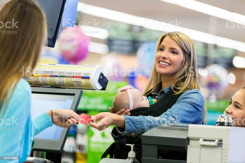 Customer using loyalty card or credit card at supermarket stock photo