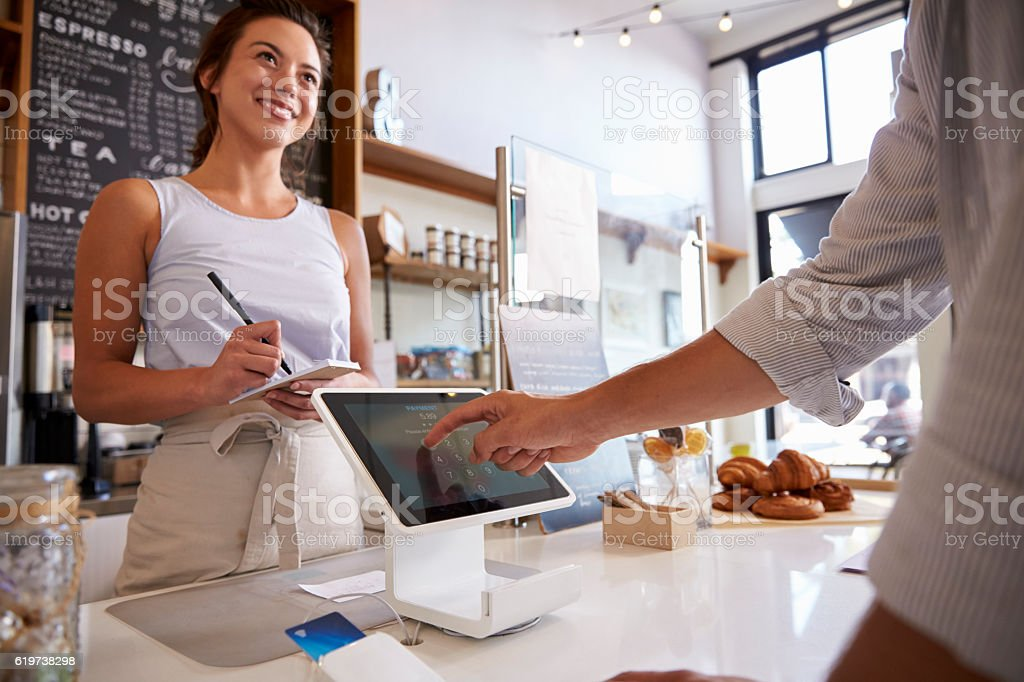 Customer using touch screen to make payment at a coffee stock photo