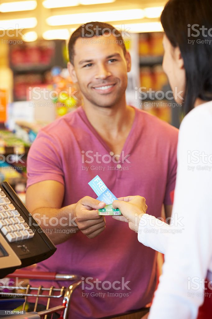 Customer Using Vouchers At Supermarket Checkout Smiling-NOTE