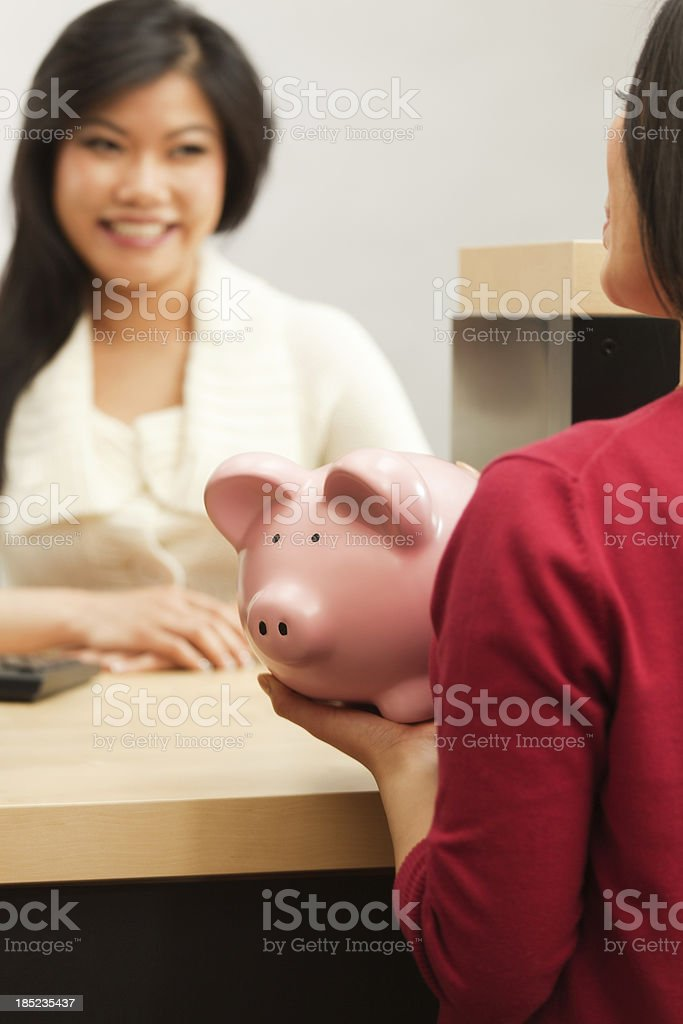 Customer with Piggy Bank Saving in Banking Teller Counter stock photo