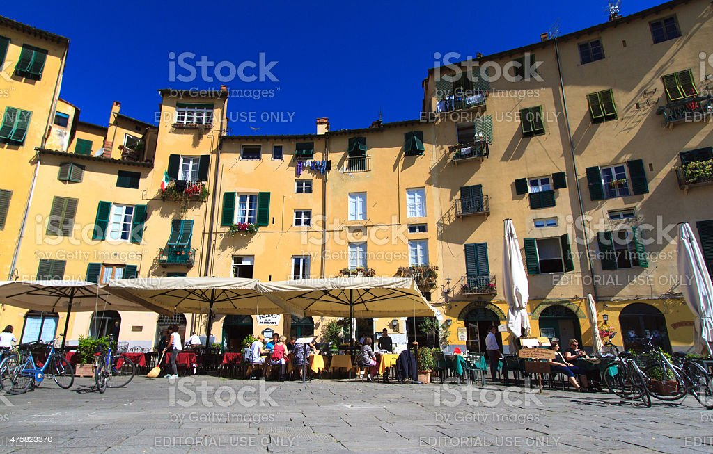 Customers at Outdoor Tables in Piazza dell'Anfiteatro in Lucca, Italy stock photo