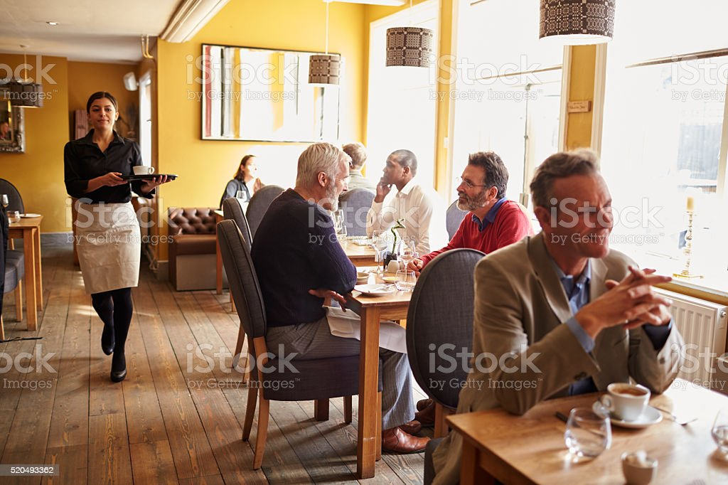 Customers at tables and waitress in busy restaurant interior stock photo