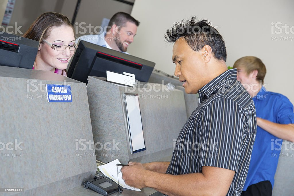 Customers at the bank getting money from tellers stock photo